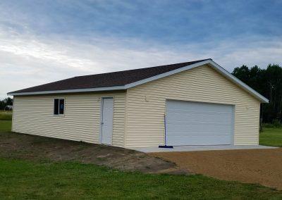 Upgrades Shown: Vinyl Siding - Concrete Apron - 3 J-Blocks - Prefinished Service Door - 4′ x 4′ Window - Ridge Vent