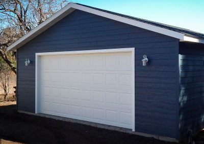 Upgrades Shown: Aluminum Soffit and Fascia - 8′ High Garage Door - LP SmartSide Prefinished Siding - Lights by Owner