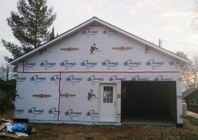 Upgrades Shown: Aluminum Soffit and Fascia - House Wrap Prepared for Homeowner Siding - Upgraded Service Door - 9′ x 7′ Garage Door Opening Prepped for Homeowner Installation - 10′ Wall  - 6/12 Pitch Roof