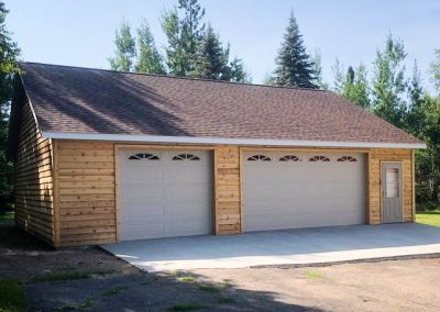 Upgrades Shown: Cedar Siding - 8′ High Garage Doors with Window Sections - Upgraded Service Door - Aluminum Soffit and Fascia  - 8/12 Pitch Roof - Driveway - Ridge Vent